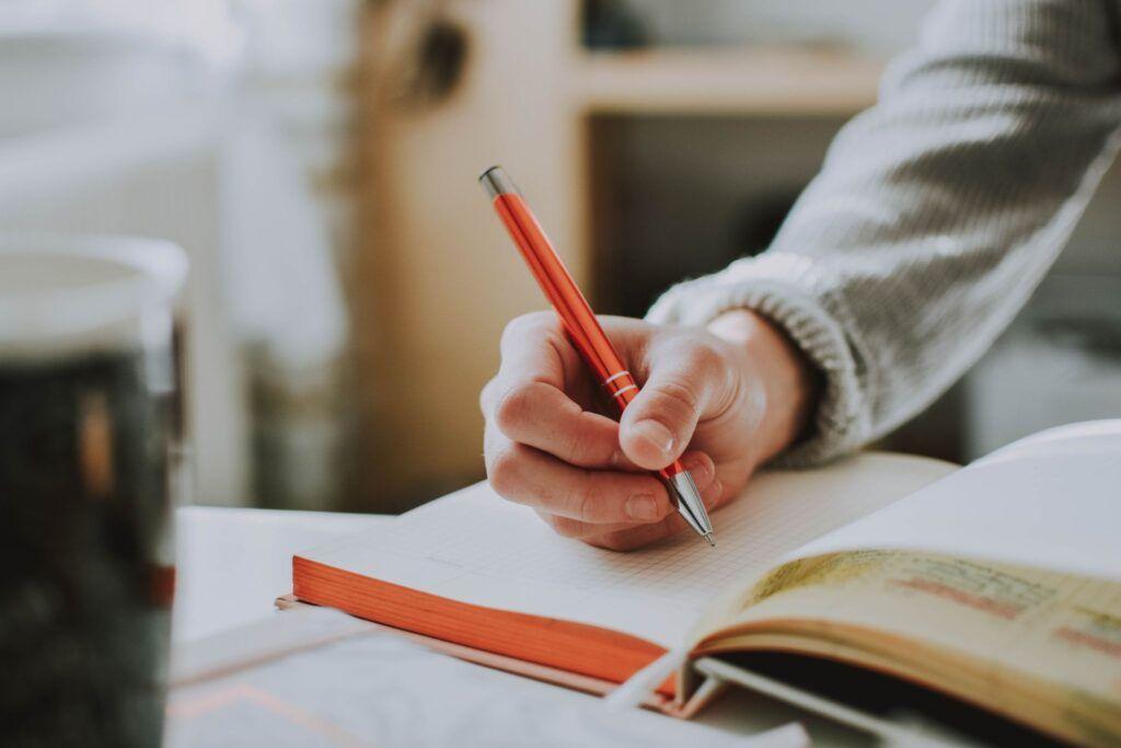 Person skriver med kuglepen i en notesbog