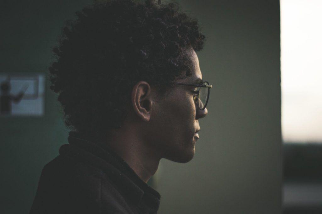 Person med krøllet hår og briller kigger ud